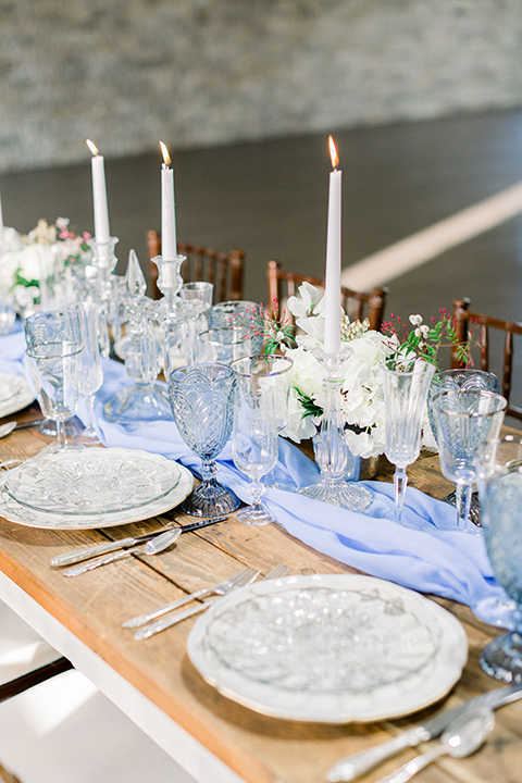 wooden table with light blue linens and tall white candles