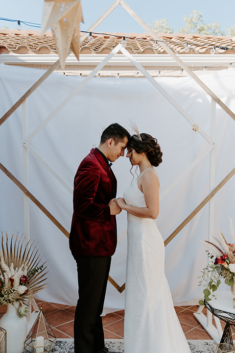 bride in a white lace gown with a drop back detail and an illusion neckline and gold modern crown and the groom in a burgundy velvet tuxedo with a black shirt