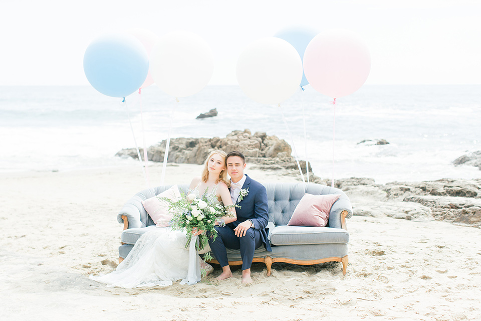 bride in a white lace gown with a v neck line and straps and the groom in a dark blue suit with a white bow tie sitting on a couch with balloons behind them