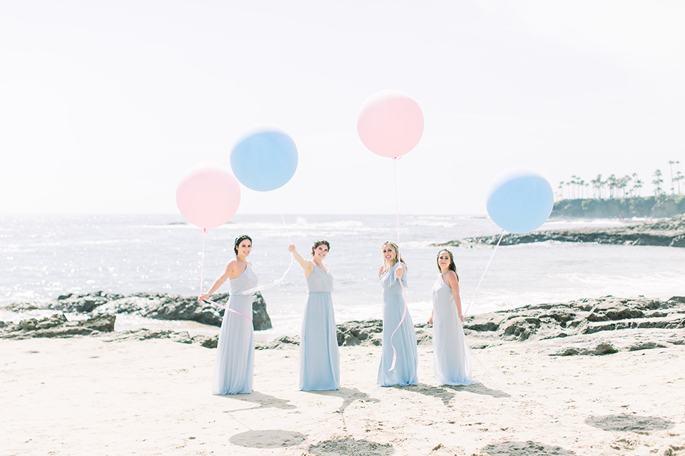 bride in a white lace gown with a v neck line and straps and the bridesmaids in light blue dresses
