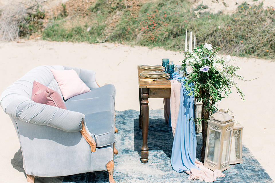 light blue couch and gold table and candle decor