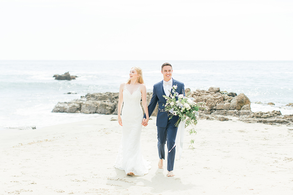 bride in a white lace gown with a v neck line and straps and the groom in a dark blue suit with a white bow tie walking