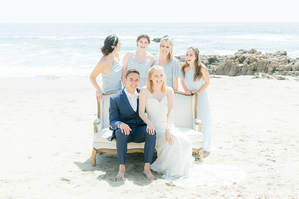 bride in a white lace gown with a v neck line and straps and the groom in a dark blue suit with a white bow tie walking with bridesmaids in light blue dresses