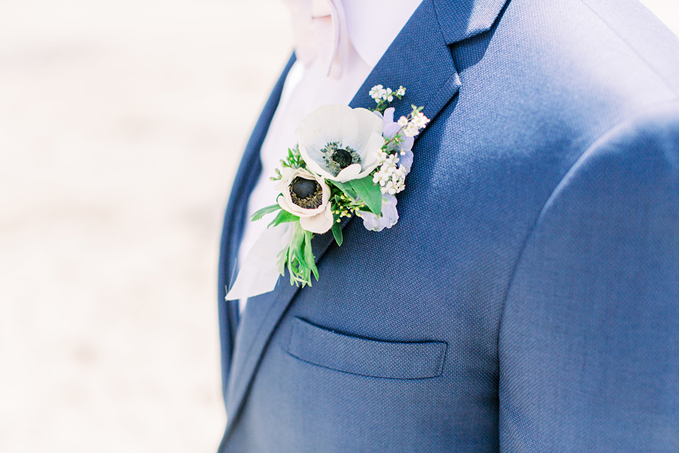 groom in a dark blue suit with a bow tie