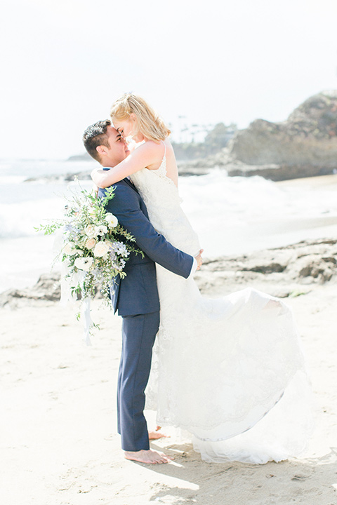 bride in a white lace gown with a v neck line and straps and the groom in a dark blue suit with a white bow tie touching heads