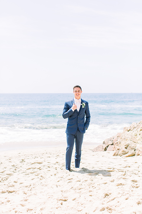 groom in a dark blue suit with a white bow tie