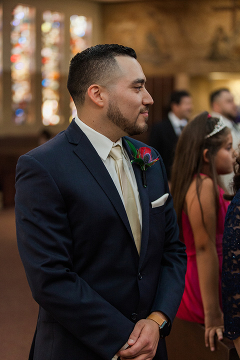 groom in a blue suit watching bride walk down the aisle