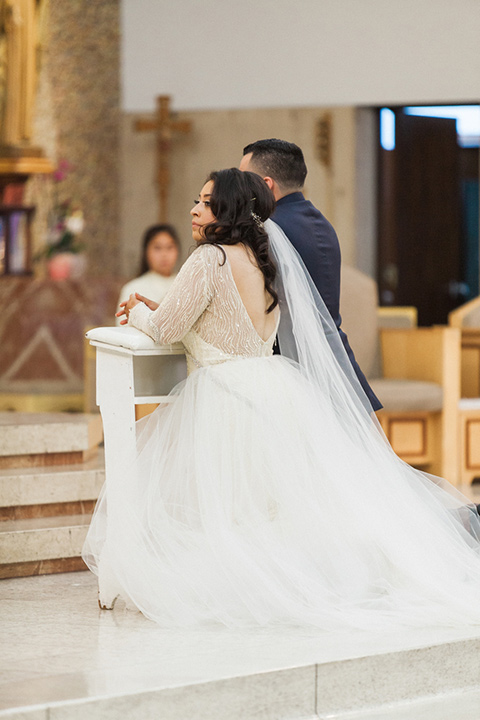 bride in an ivory ballgown with gold trim and groom in navy suit sitting during ceremony in church
