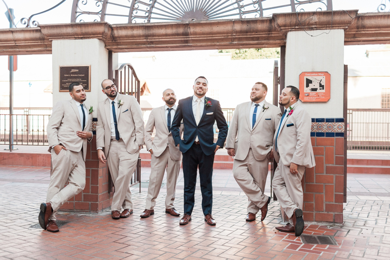 bridalparty with groom in navy, groomsmen in tan the bride in ivory and the bridesmaids in navy