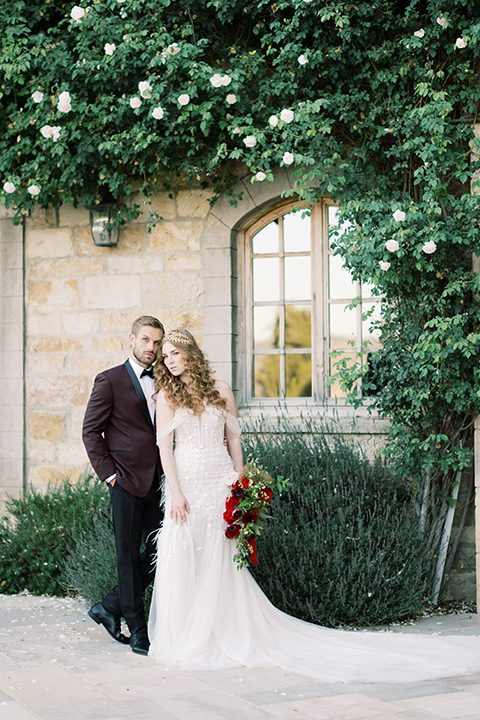 bride in a lace formfitting gown with an off the shoulder detail and the groom in a burgundy tux and black bow tie