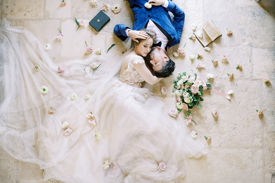 bride in a white long ball gown with tulle train and long cathedral veil and the groom in a blue velvet tuxedo with a black bow tie