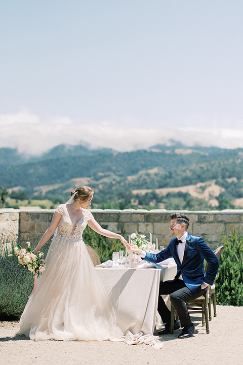 bride in a white long ball gown with tulle train and long cathedral veil and the groom in a blue velvet tuxedo