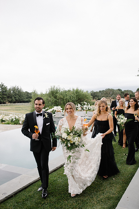 bride in a white gown with floral appliques and trumpet sleeves, the bridesmaids in black dresses in all different styles