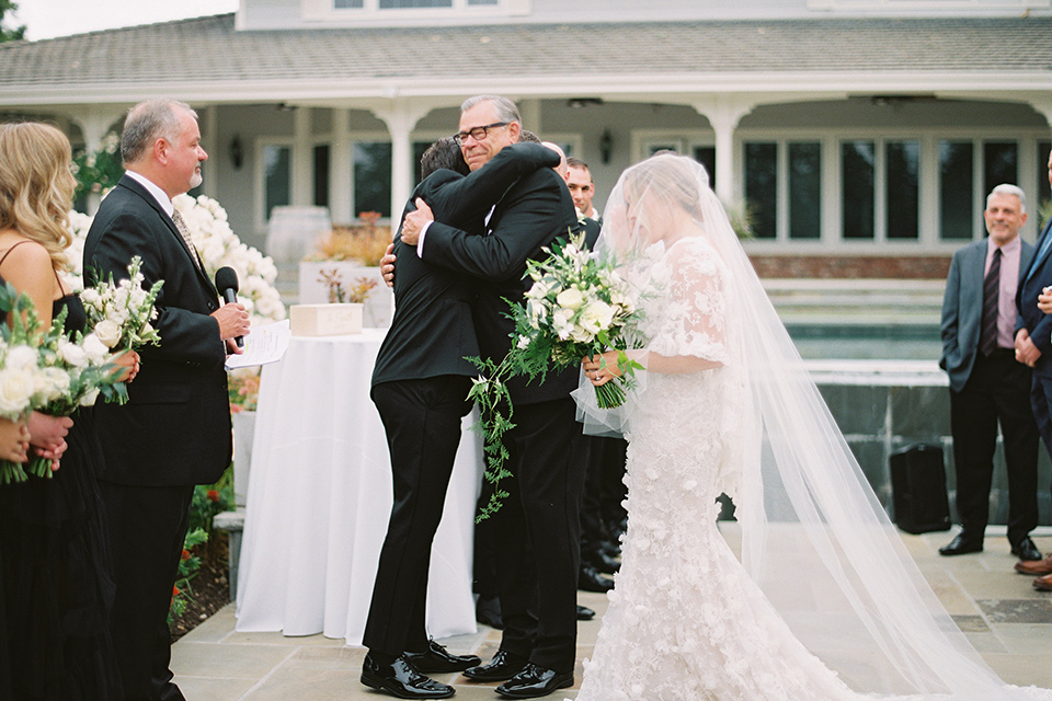 bride in a white gown with floral appliques and trumpet sleeves, the bridesmaids in black dresses in all different styles and the groom + groomsmen in black tuxedos and black bow ties