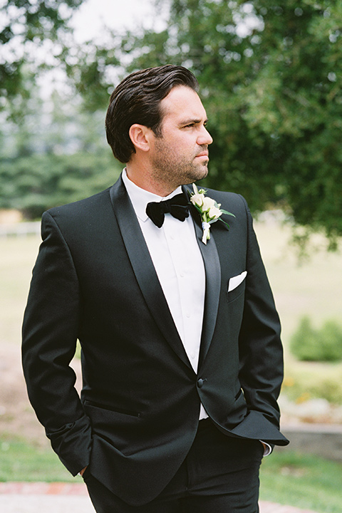 bride in a white gown with floral appliques and trumpet sleeves, the groom in a black tuxedo with black tie accessories