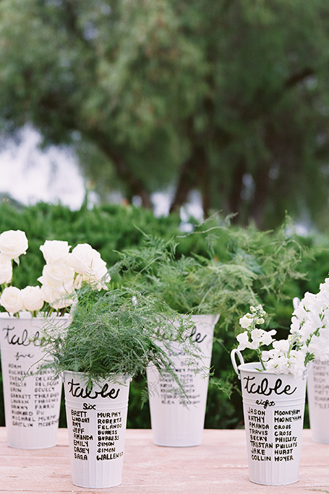 white flower pots with writing for the table numbers