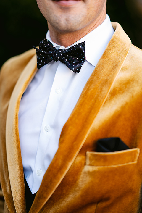the groom in a gold velvet tuxedo with black pants and black bow tie