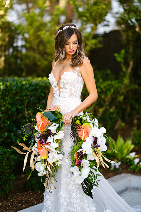 bride in a formfitting white lace gown with a sweetheart neckline and bold bouquet