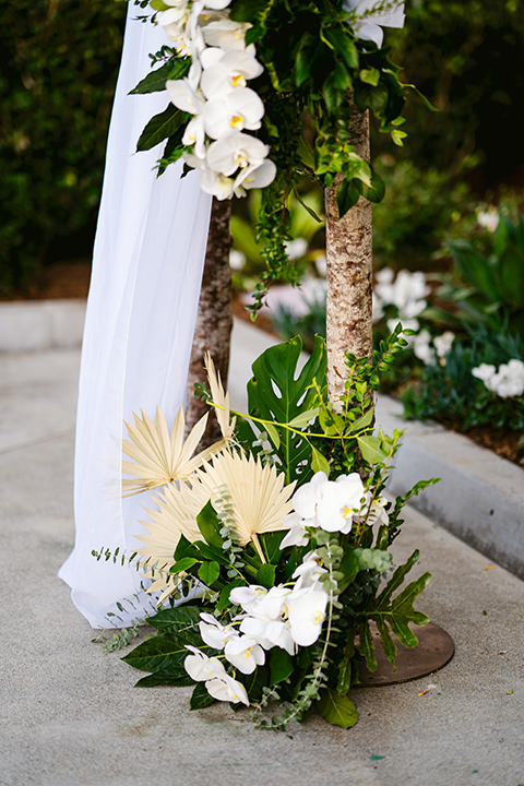 white florals and white linens at ceremony arch
