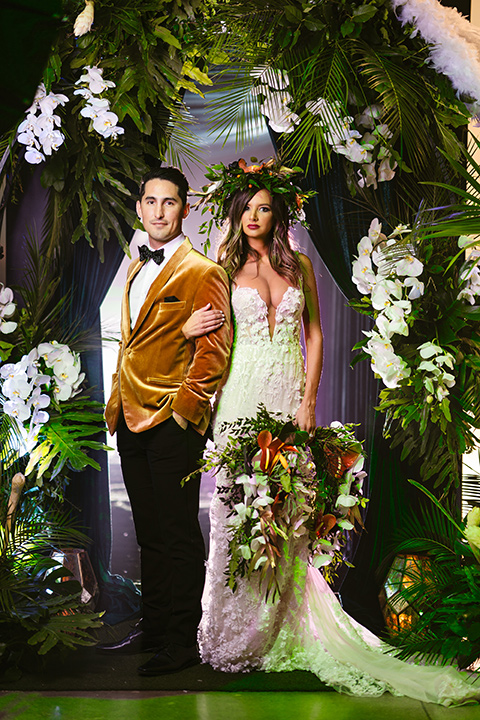bride in a formfitting white lace gown with a sweetheart neckline and bold bouquet and the groom in a gold velvet tuxedo with black pants and black bow tie