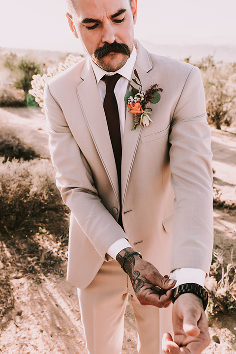 the groom in a tan suit with a burgundy tie and suspenders