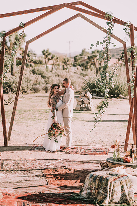 bride in a formfitting gown with lace and a floral crown, the groom in a tan suit with a burgundy tie and suspenders kissing