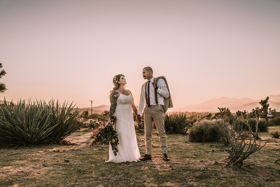 bride in a formfitting gown with lace and a floral crown, the groom in a tan suit with a burgundy tie and suspenders