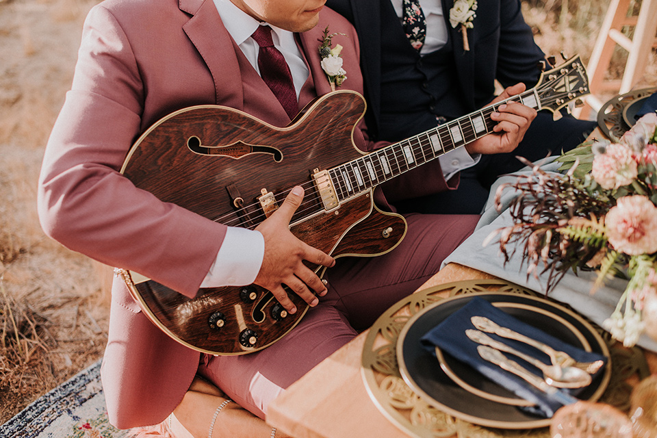 groom in a pink suit with a deep burgundy bow long tie and the other groom in a dark blue suit with a floral long tie at the table with a guitar