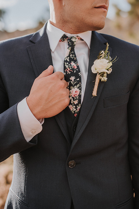 groom in a blue suit and a floral long tie