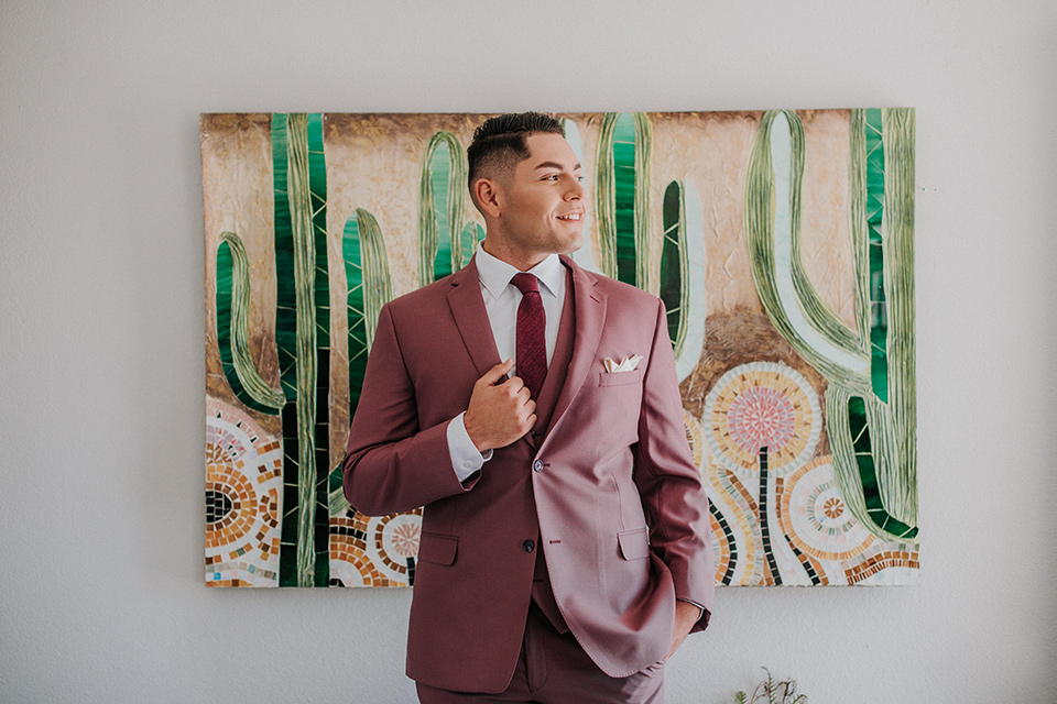 groom in a pink suit with a deep burgundy bow long tie
