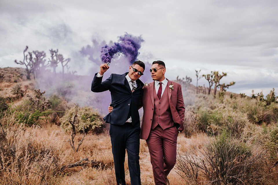 groom in a pink suit with a deep burgundy bow long tie and the other groom in a dark blue suit with a floral long tie