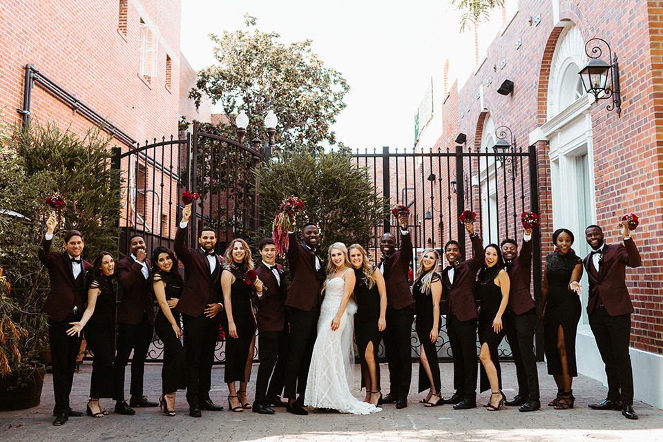 bride in a formfitting lace white gown with thin straps, and the groom in a burgundy tuxedo with a black bow tie.  The bridesmaids in black tea length gowns and the groomsmen in burgundy tuxedos