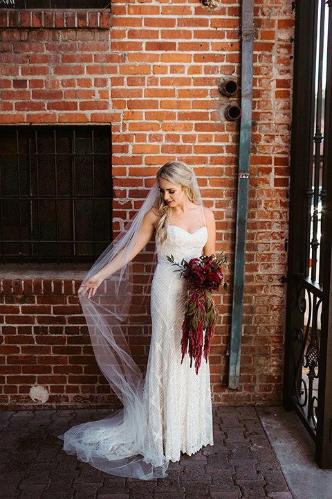 bride in a white formfitting gown with thin lace straps and cathedral veil