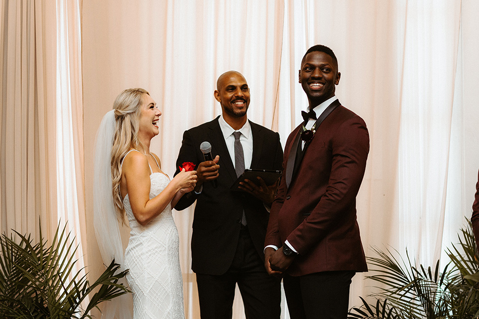 bride in a formfitting lace white gown with thin straps, and the groom in a burgundy tuxedo with a black bow tie.