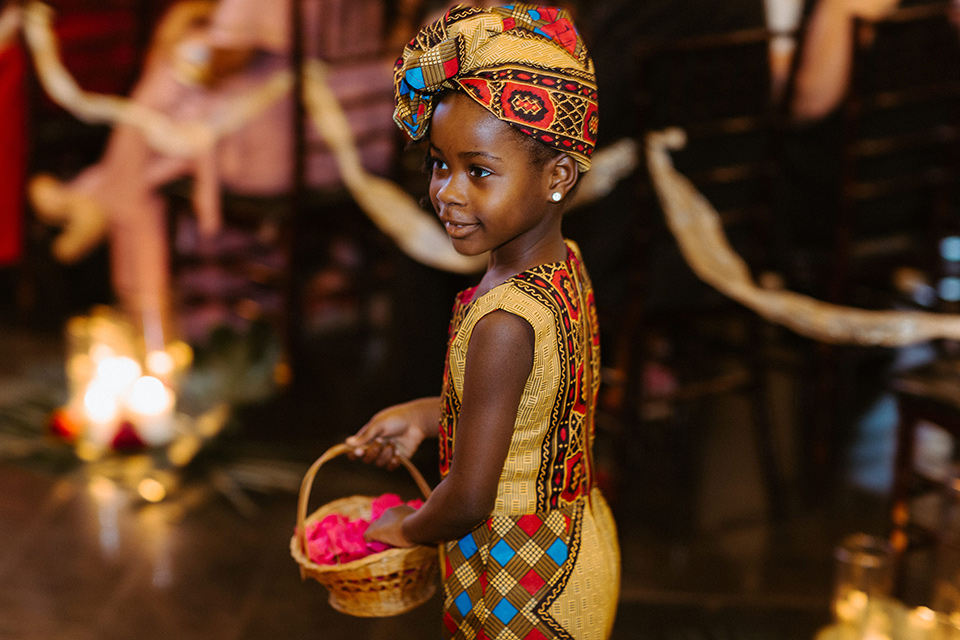 flower girl in a yellow African dress and headpiece