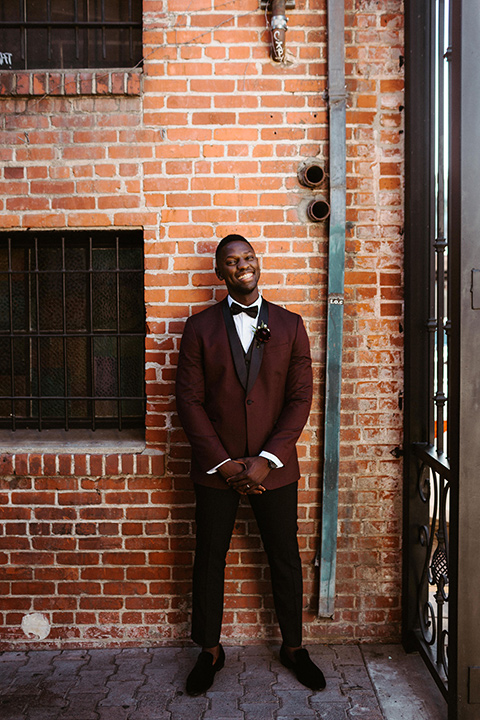 groom in a burgundy tuxedo and black bow tie
