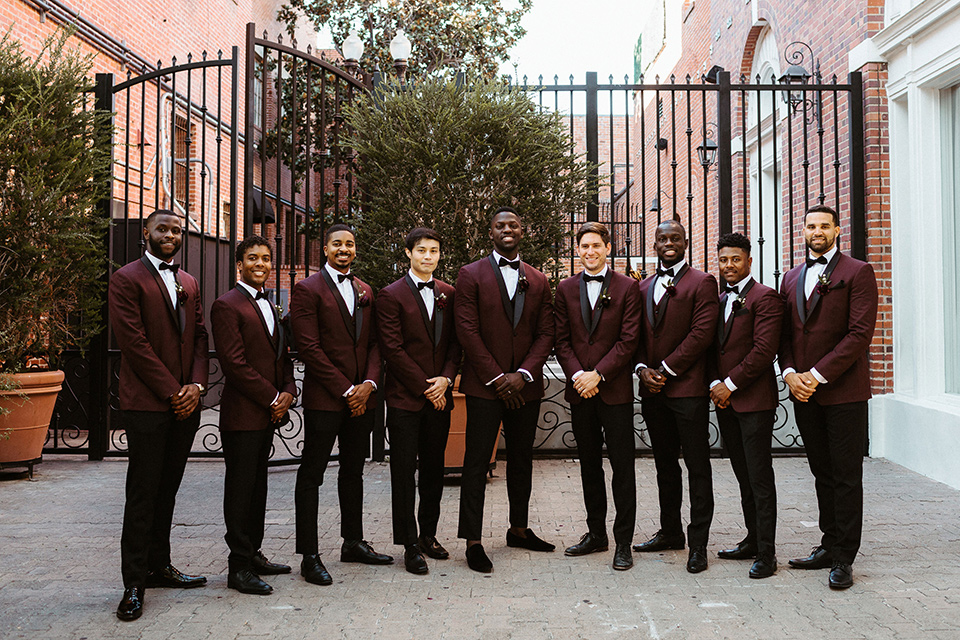 the groom in a burgundy tuxedo with a black bow tie and the groomsmen in burgundy tuxedos