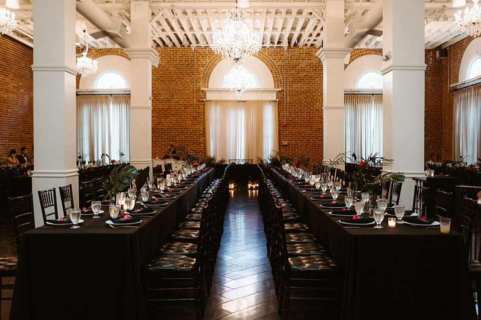 brick style venue with long tables covered in black linens and gold accessories