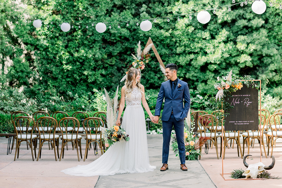 bride in a lace formfitting gown with a high neckline and the groom in a cobalt blue suit with a black shirt and blue long tie at ceremony