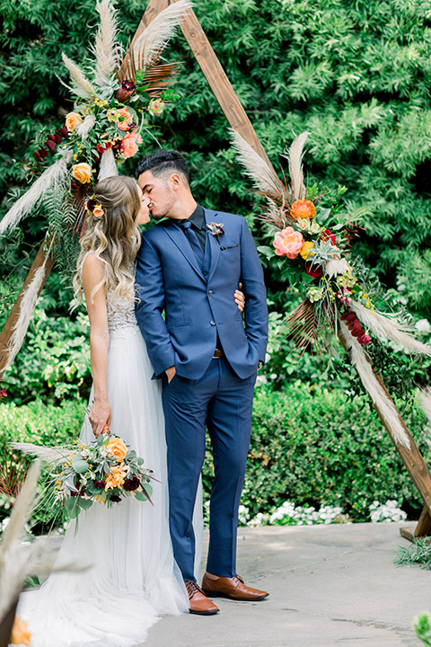 bride in a lace formfitting gown with a high neckline and the groom in a cobalt blue suit with a black shirt and blue tie