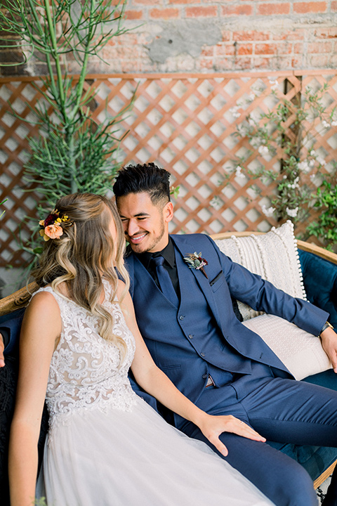 bride in a lace formfitting gown with a high neckline and the groom in a cobalt blue suit with a black shirt and blue long tie