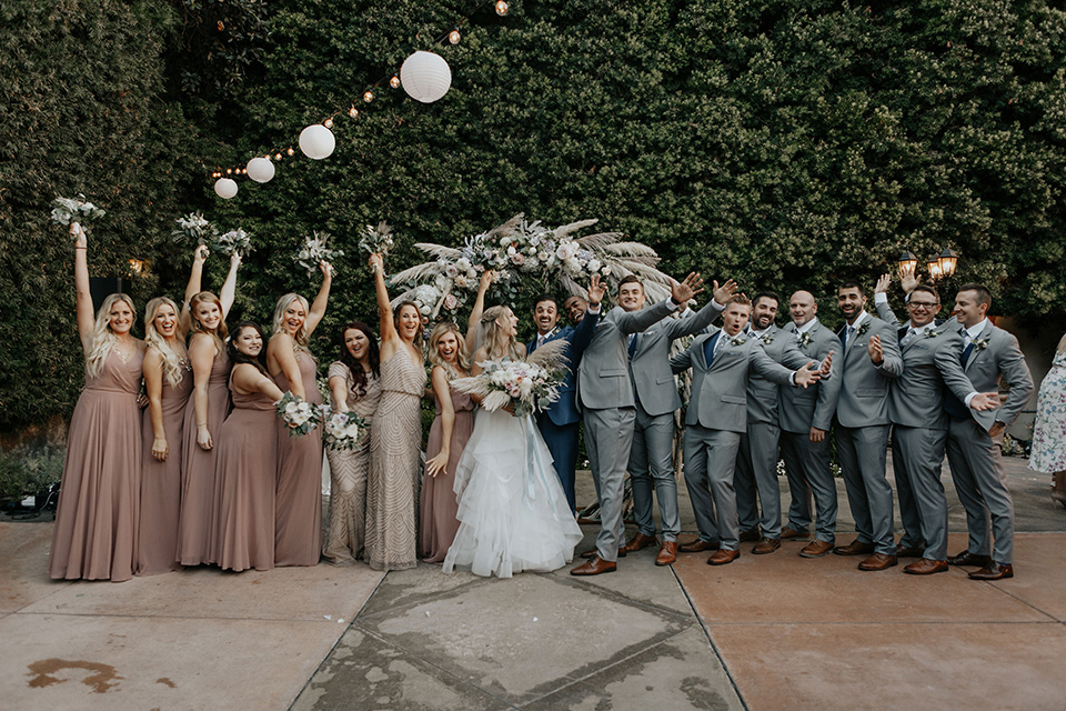 bride in a white ballgown and lace bodice detailing, the groom in a dark blue suit with a pink long tie.  The bridesmaids in pink dresses and groomsmen in light grey suits with dark blue vests