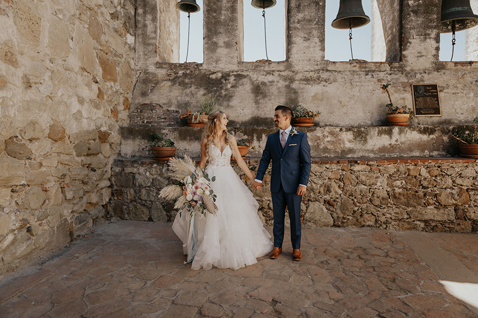 bride in a white ballgown and lace bodice detailing, the groom in a dark blue suit with a pink long tie