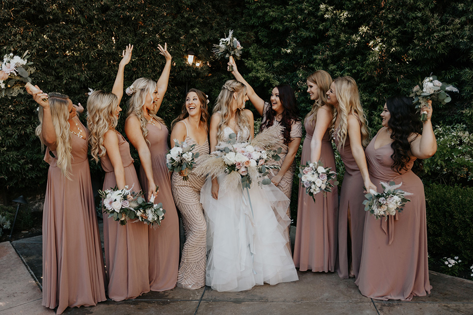 bride in a white ballgown and lace bodice detailing, bridesmaids in light pink and mauve toned gowns