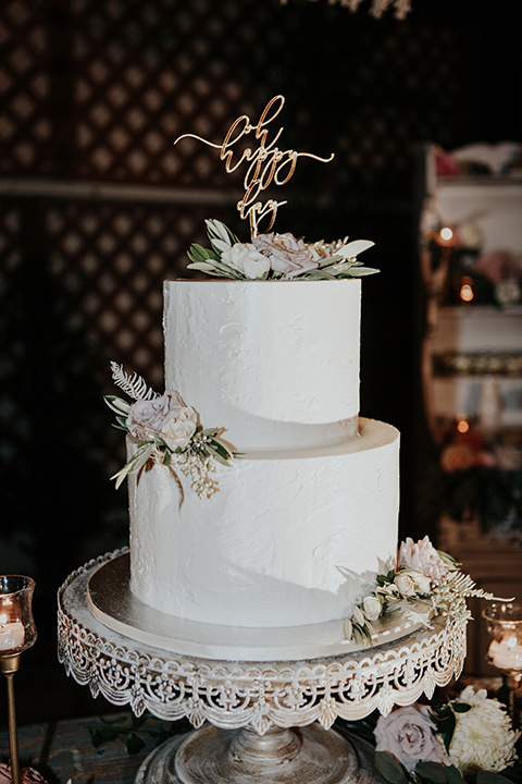 white two-tiered cake with light pink floral detailing