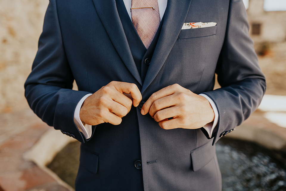 groom in a dark blue suit and a light pink long tie