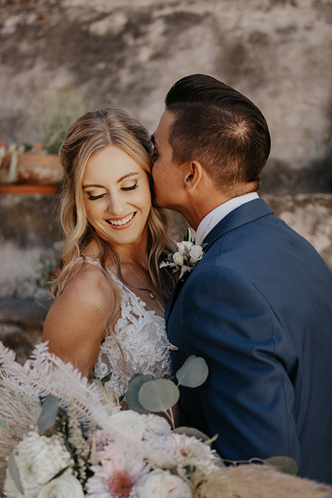 bride in a white ballgown and lace bodive and the groom in a dark blue suit with a light pink suit