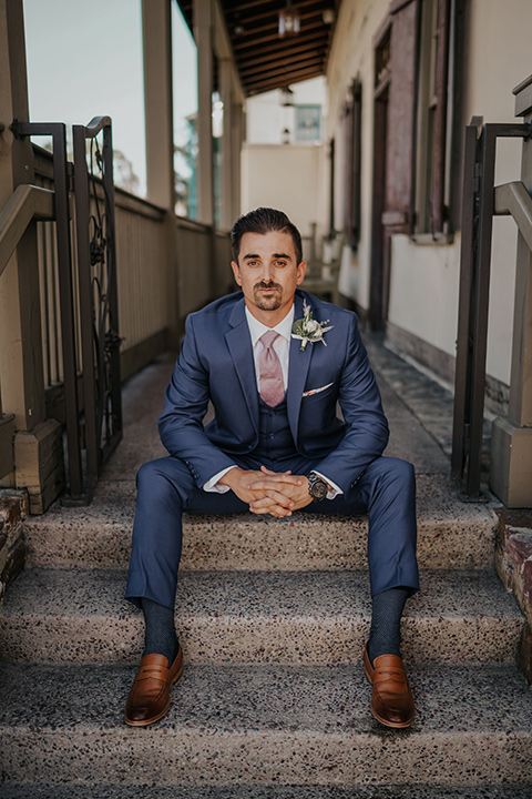 groom in a dark blue suit with a light pink suit