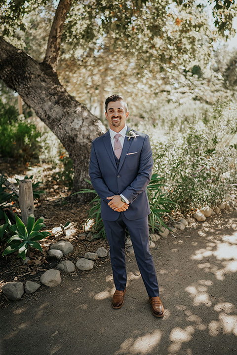 groom in a dark blue suit and light pink long tie