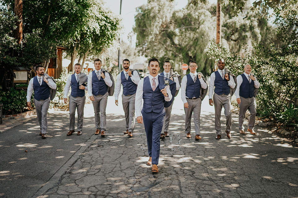 the groom in a dark blue suit with a pink long tie and groomsmen in light pink suits with a dark blue vest